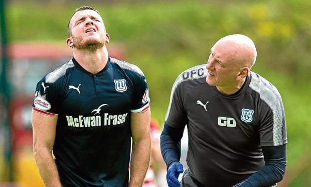 Dundee winger Randy Wolters is treated by physio Gerry Docherty after hamstring trouble before being replaced in the 33rd-minute against Hamilton