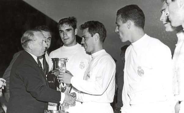 Uefa president Ebbe Schwartz presents the European Cup to Jose Zarraga, captain of Real Madrid.