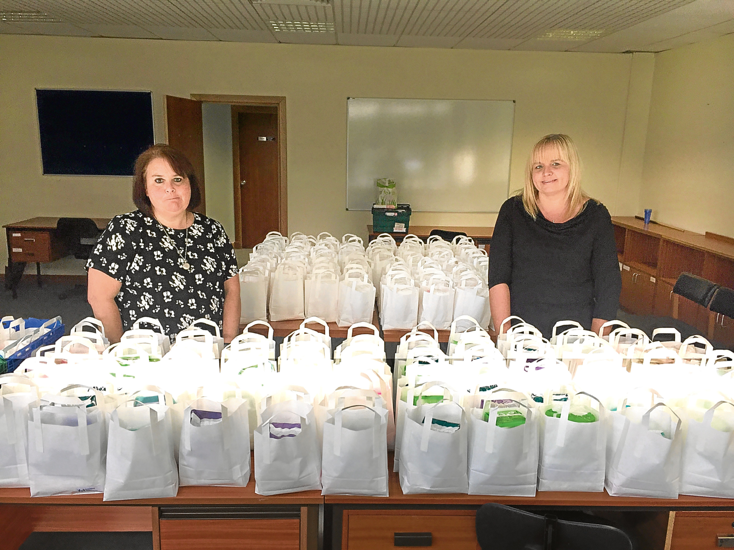 """Jane Reid and Michelle McGraw with the care packs they are set to hand out to combat the ongoing period poverty """"crisis""""."""