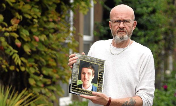 Phil Welsh with a photo of his son Lee.