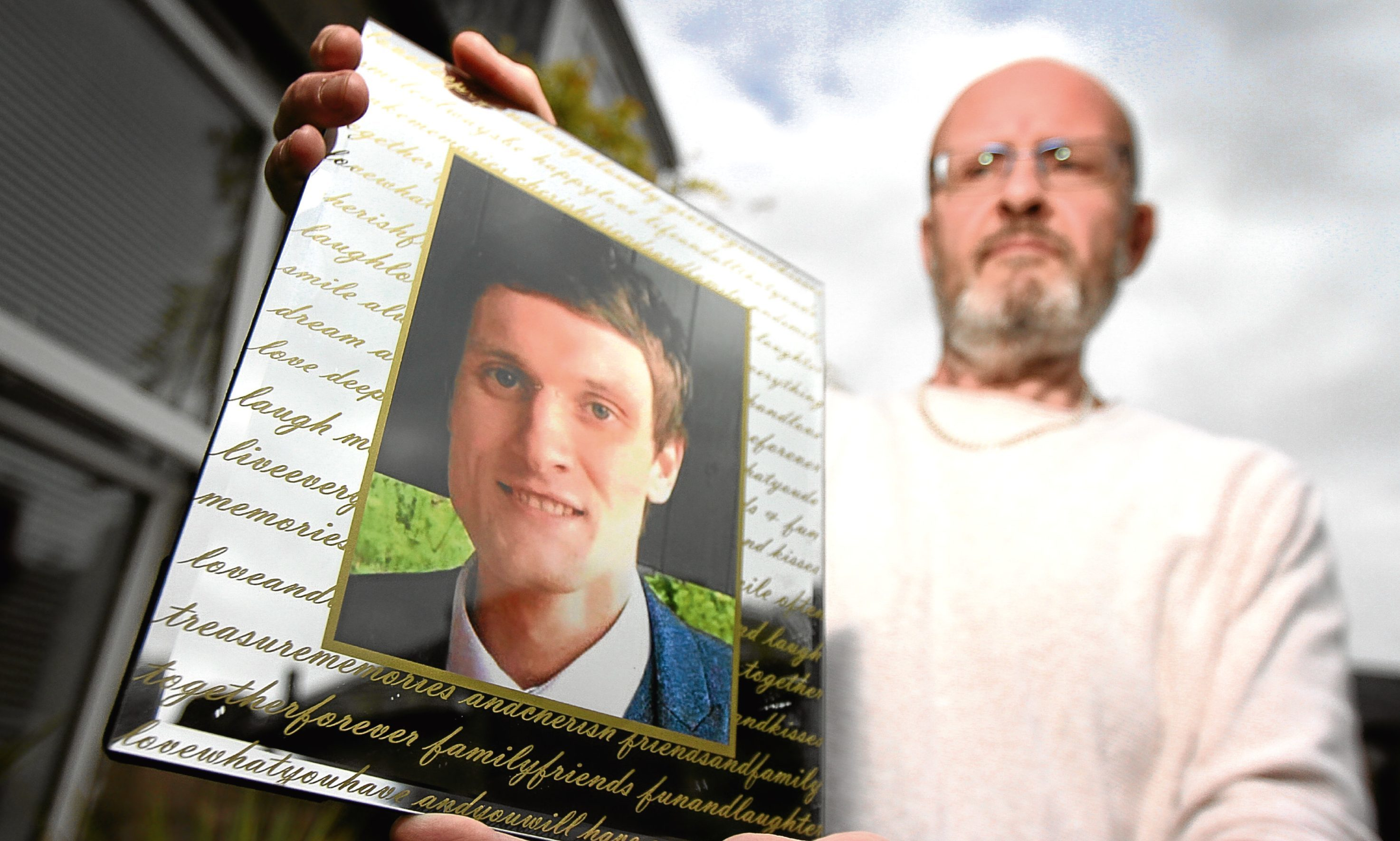 Phil Welsh holding a photo of son Lee, who died last month