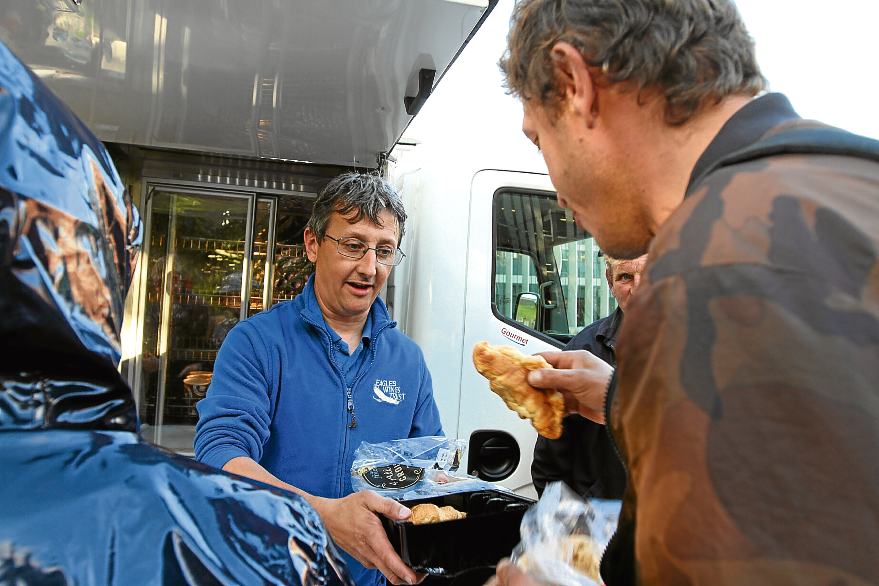 Eagles Wings Trust founder Mike Cordiner serves food and coffee from its van.