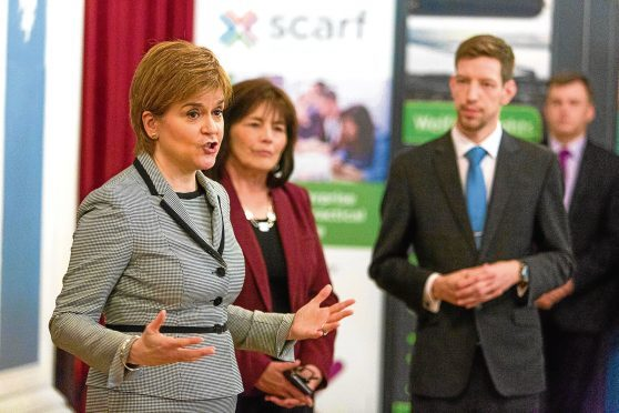 Council leader John Alexander looks on as First Minister Nicola Sturgeon announces a benefits jobs boost for Dundee.