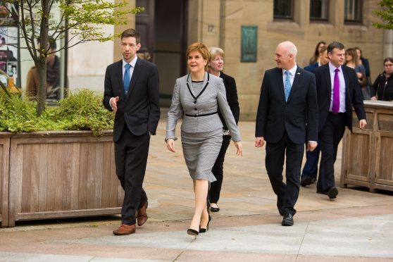 Nicola Sturgeon walks alongside Dundee City Council leader John Alexander in the city on Monday.