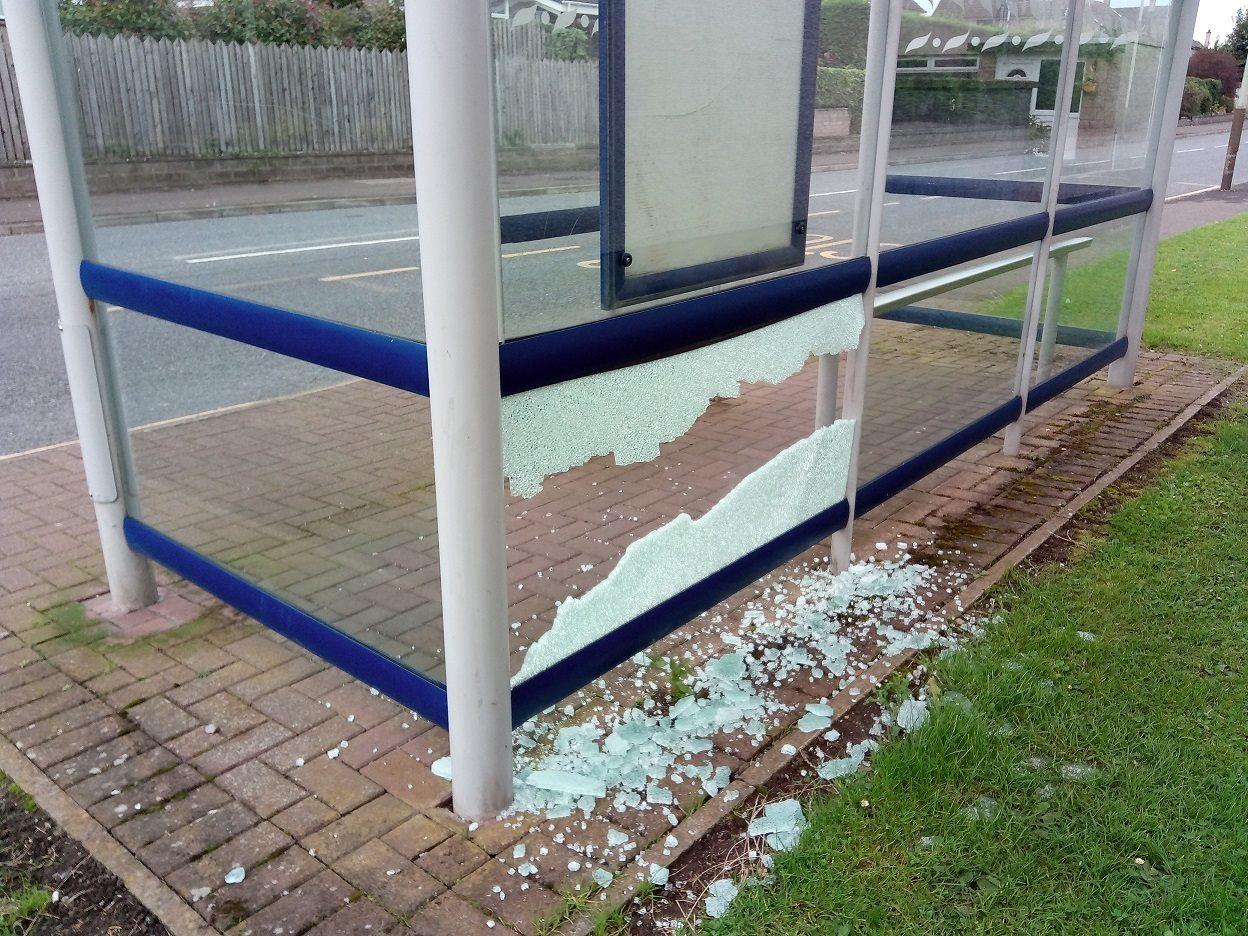 The smashed bus shelter.