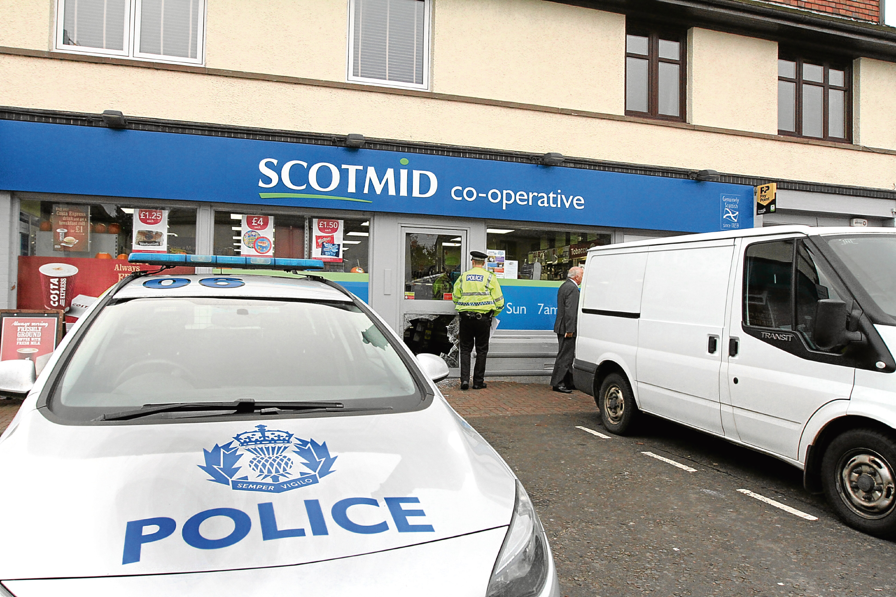 Police attend a break-in at the Scotmid store in Invergowrie, where the bottom panel of the front door was smashed