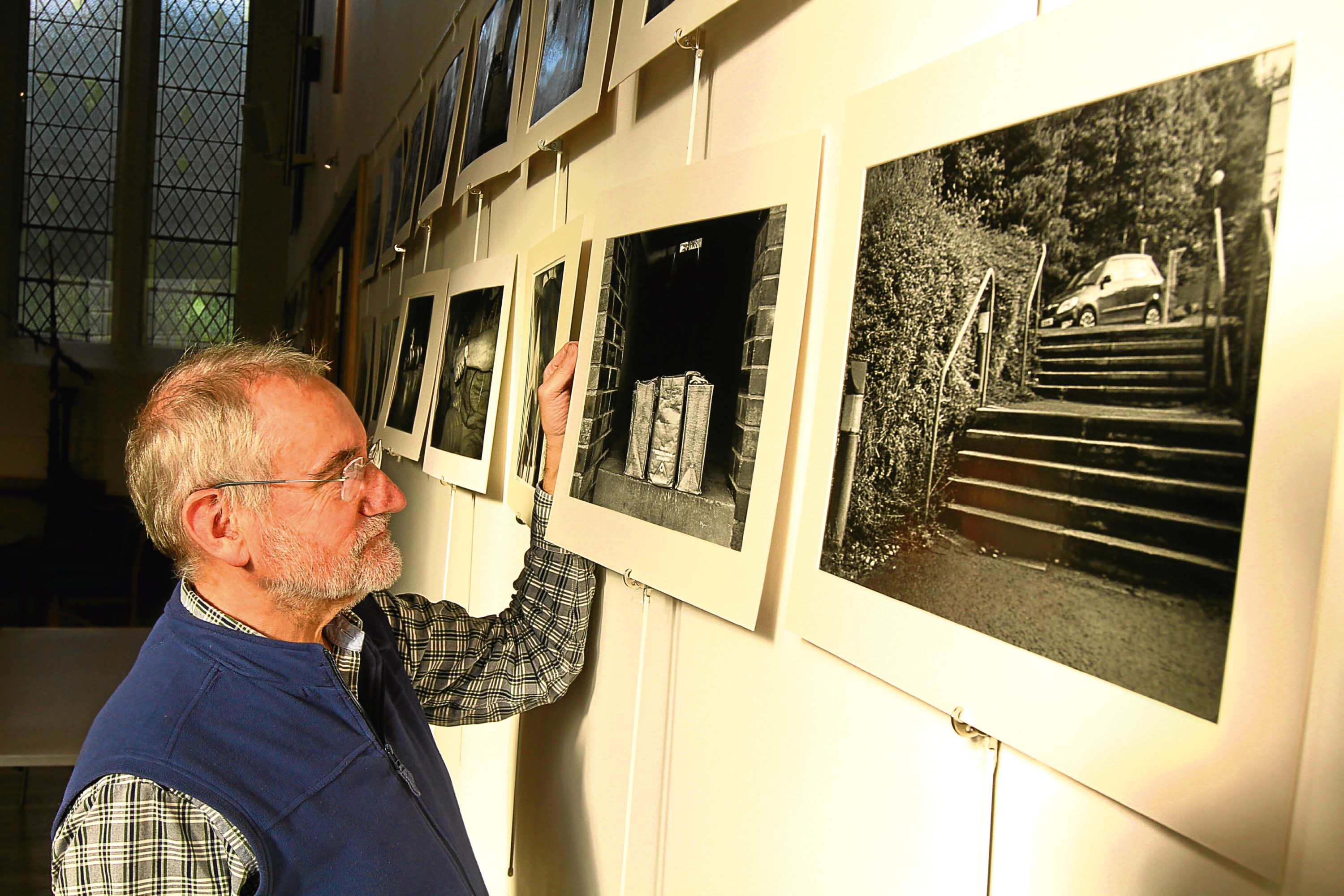 Rev Robert Calvert, looking at some of the photographs in the Developing Recovery photographic exhibition at the Steeple Church in Dundee