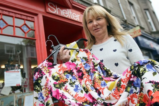 Shop manager Karen Kelbie with the dresses donated by Lorraine Kelly