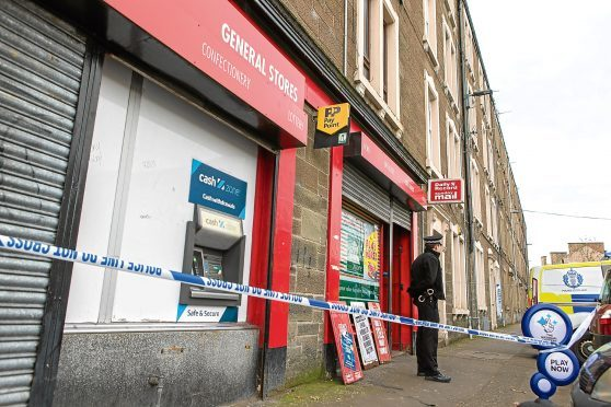 Police on the scene where the shop was robbed yesterday