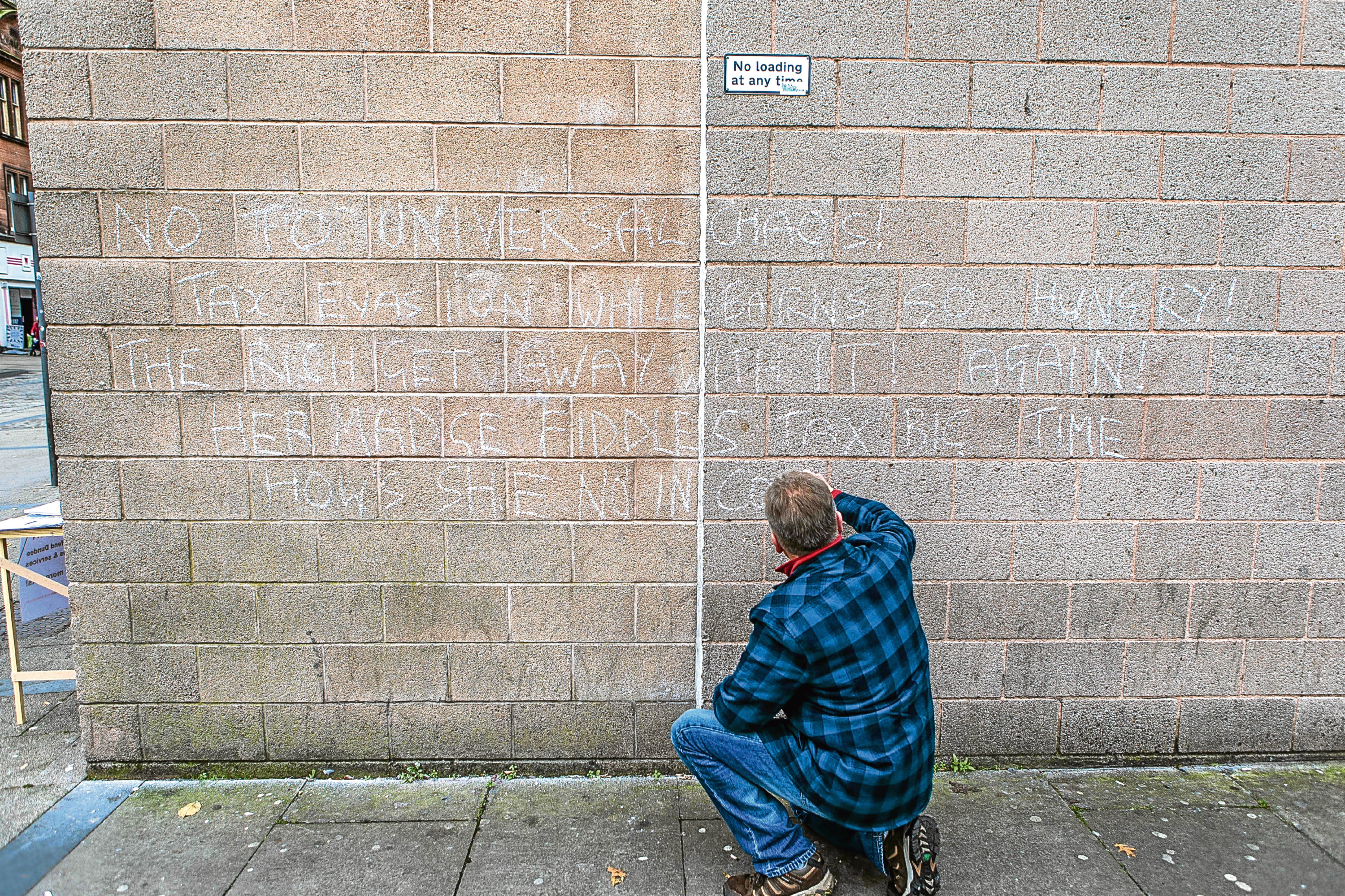 A man scrawls a message in chalk outside Dundee Job Centre in protest at Universal Credit.
