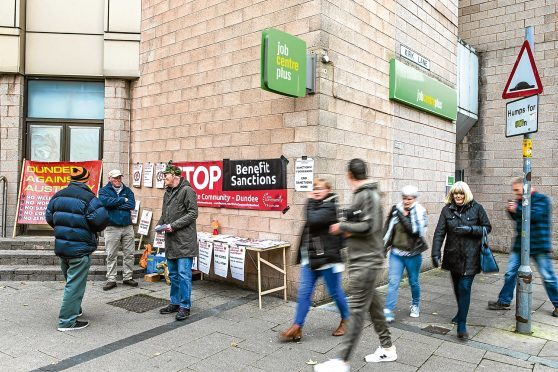 Protesters hand out leaflets outside Dundee Job Centre to raise concerns and make people aware of the recent cuts and benefits changes