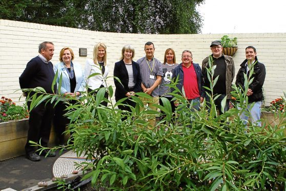 Shona Robison MSP (fourth from left) flanked by Dave Barrie and Lesley McLay, NHS Tayside chief executive, and other staff and volunteers at the opening of The Garden of Hope, at The Signpost Centre.