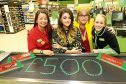 "Picture shows Chloe (second left) at Asda Kirkton to pick up the cheque for £500 with (from left) Sam, Kate Smith and Zena Dodds (both check-out assistants) and next to the total amount raised ""written"" with green tokens."