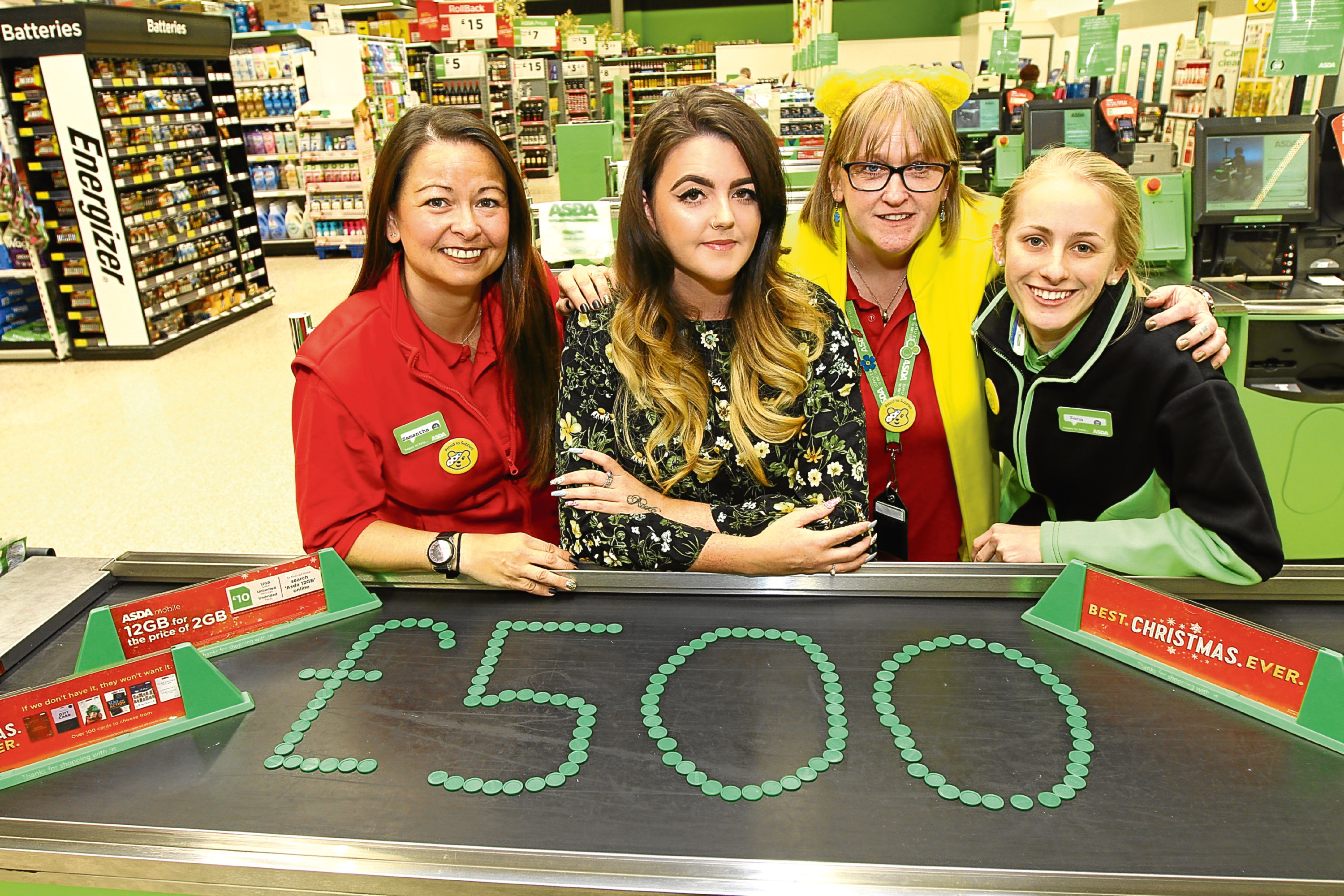 """Picture shows Chloe (second left) at Asda Kirkton to pick up the cheque for £500 with (from left) Sam, Kate Smith and Zena Dodds (both check-out assistants) and next to the total amount raised """"written"""" with green tokens."""