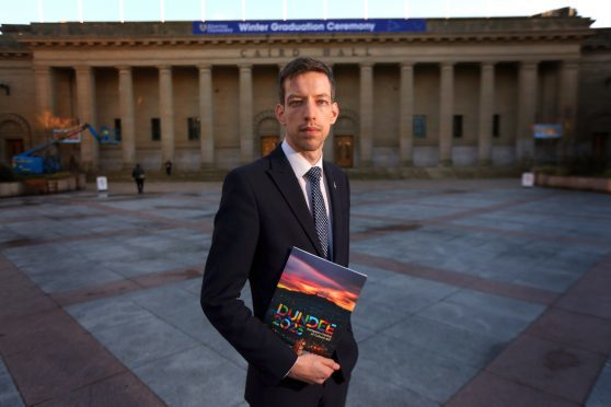 John Alexander, Leader of Dundee City Council, with the bid brochure