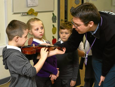 Andy Thorn of the Big Noise Project sizes up some of the kids for violas at St Pius RC Primary School.