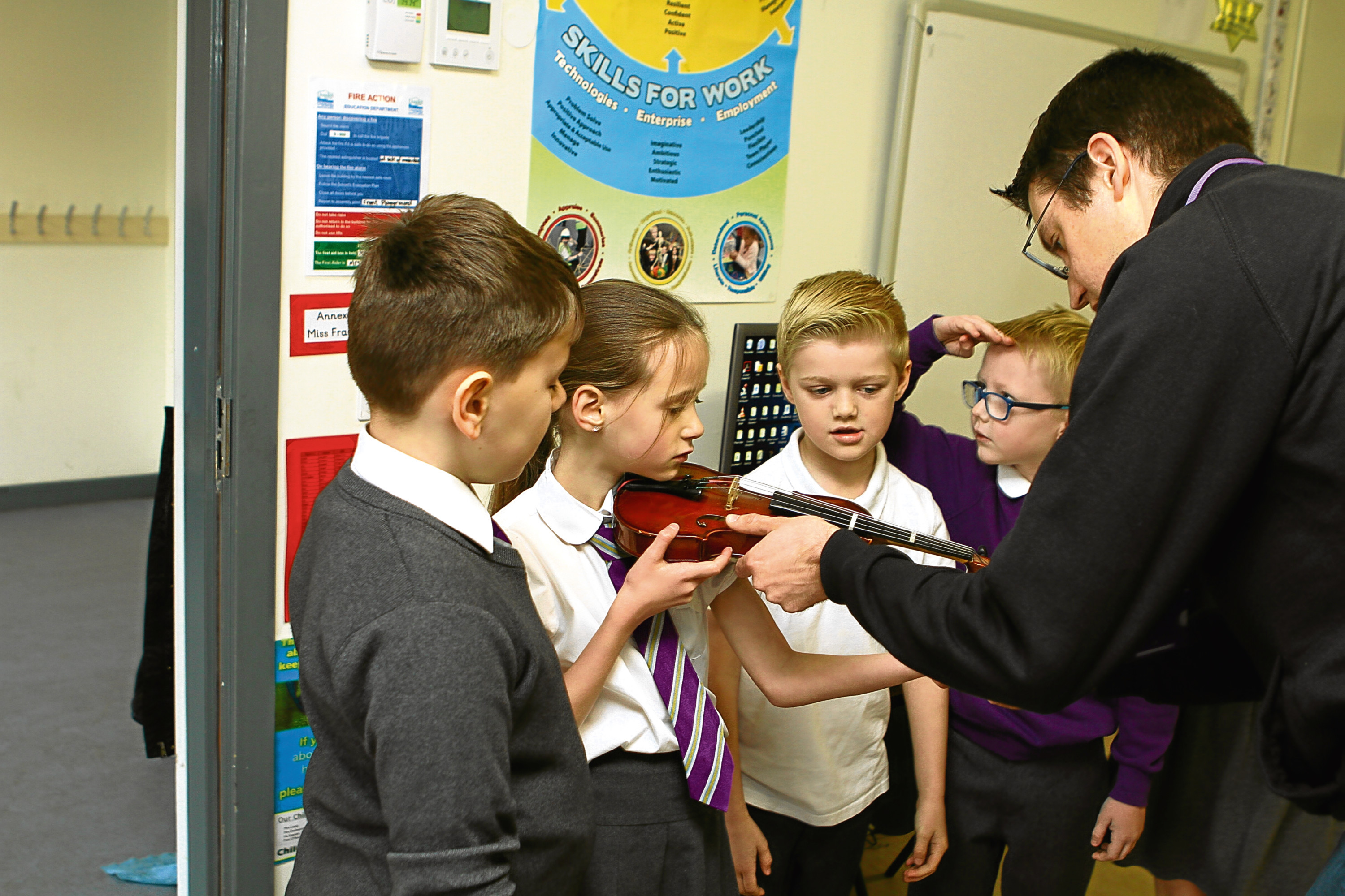 St Pius pupils are taught violin by Andy Thorn from the Big Noise Project