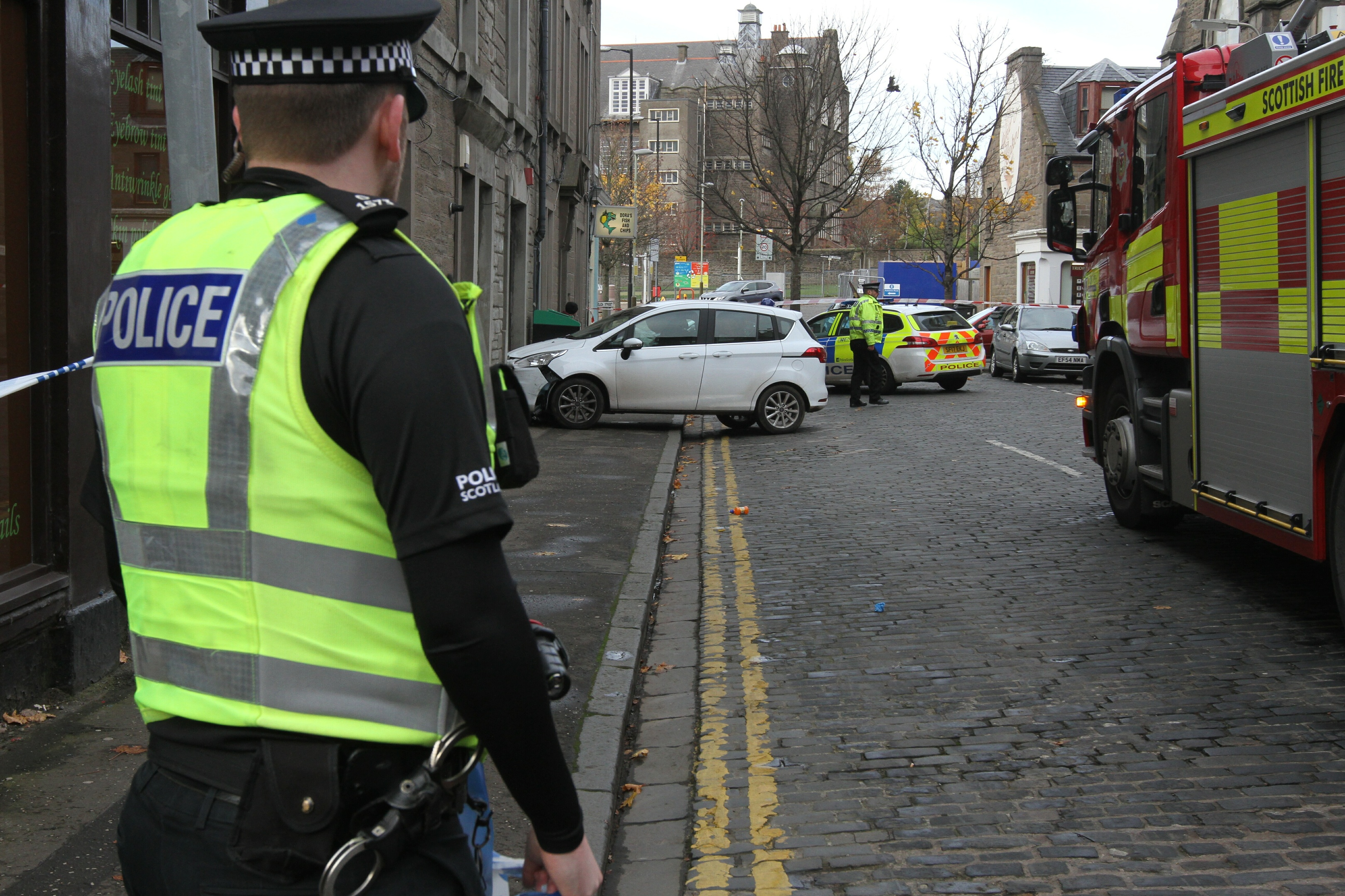 A police officer looks on at the scene of the crash on Eliza Street.