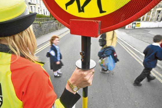 Children from Paulton Primary School cross the road as lollipop lady Helen Tilbury trials a new hi-tech lollpop stick, which has CCTV video built-in to capture any motorists who break the law or become aggressive.