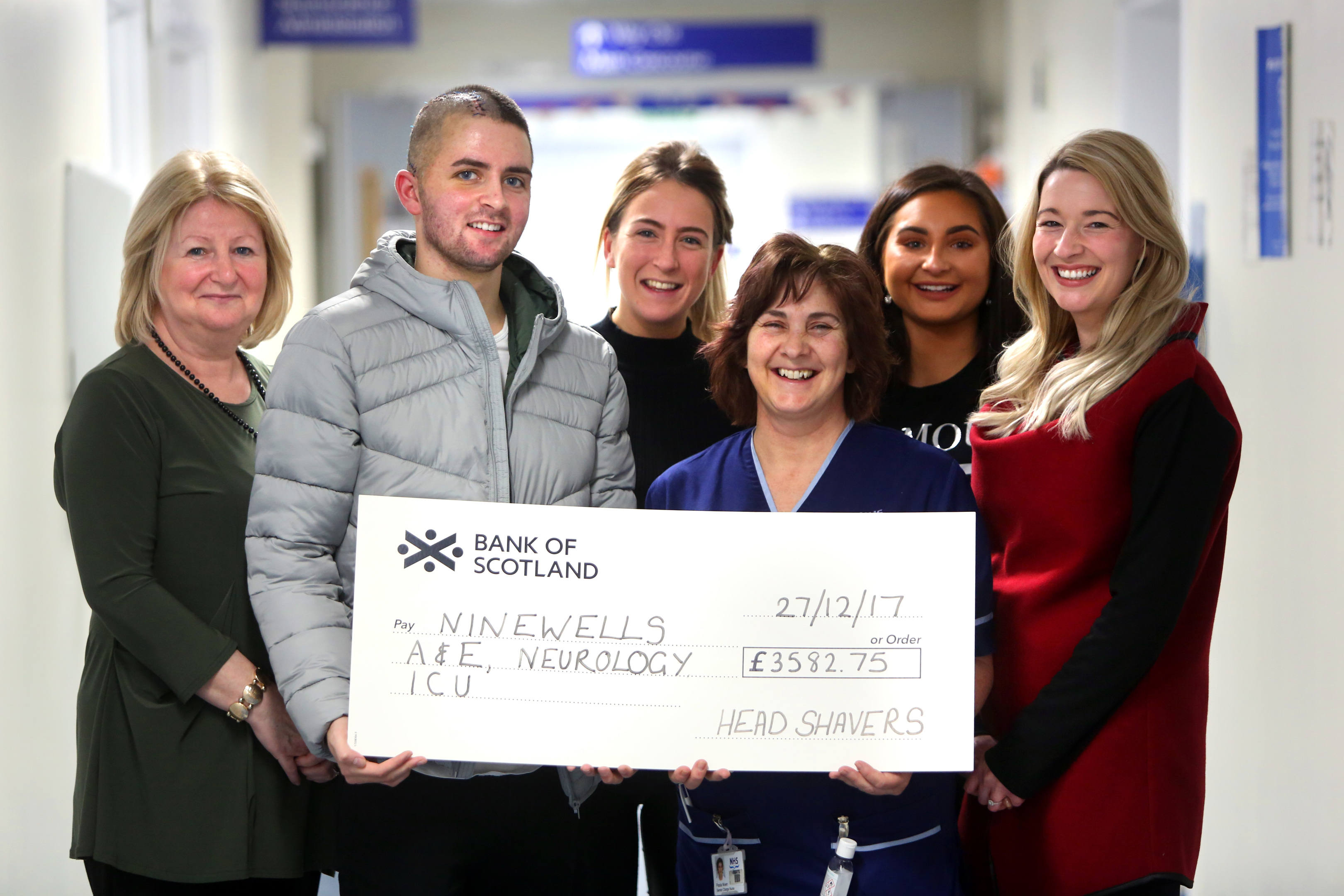 John Black hands over a cheque to charge nurse Paola Niven. Also pictured (from left to right) mum June Black, sister Jodie Black, John's girlfriend Joanna Taylor and sister Jenna Black.
