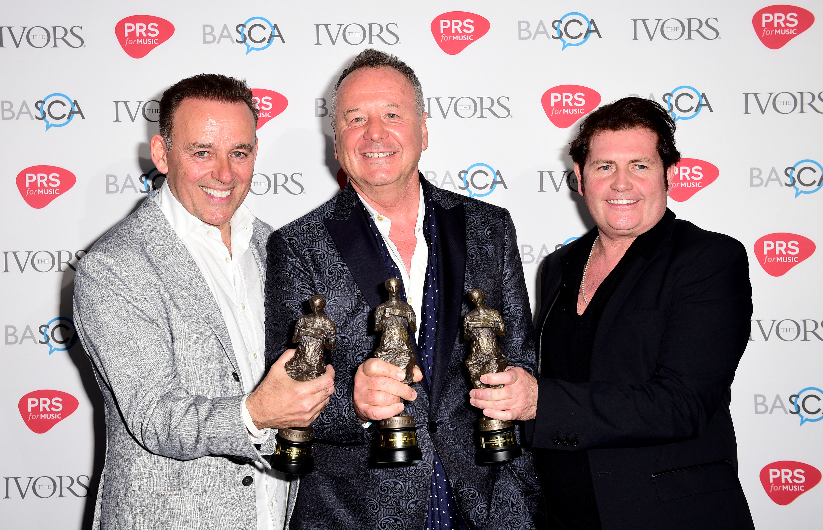 Mick MacNeil, Jim Kerr and Charlie Burchill of Simple Minds with the Outstanding Song Collection Award during the 2016 61st Annual Ivor Novello Music Awards at Grosvenor House in London