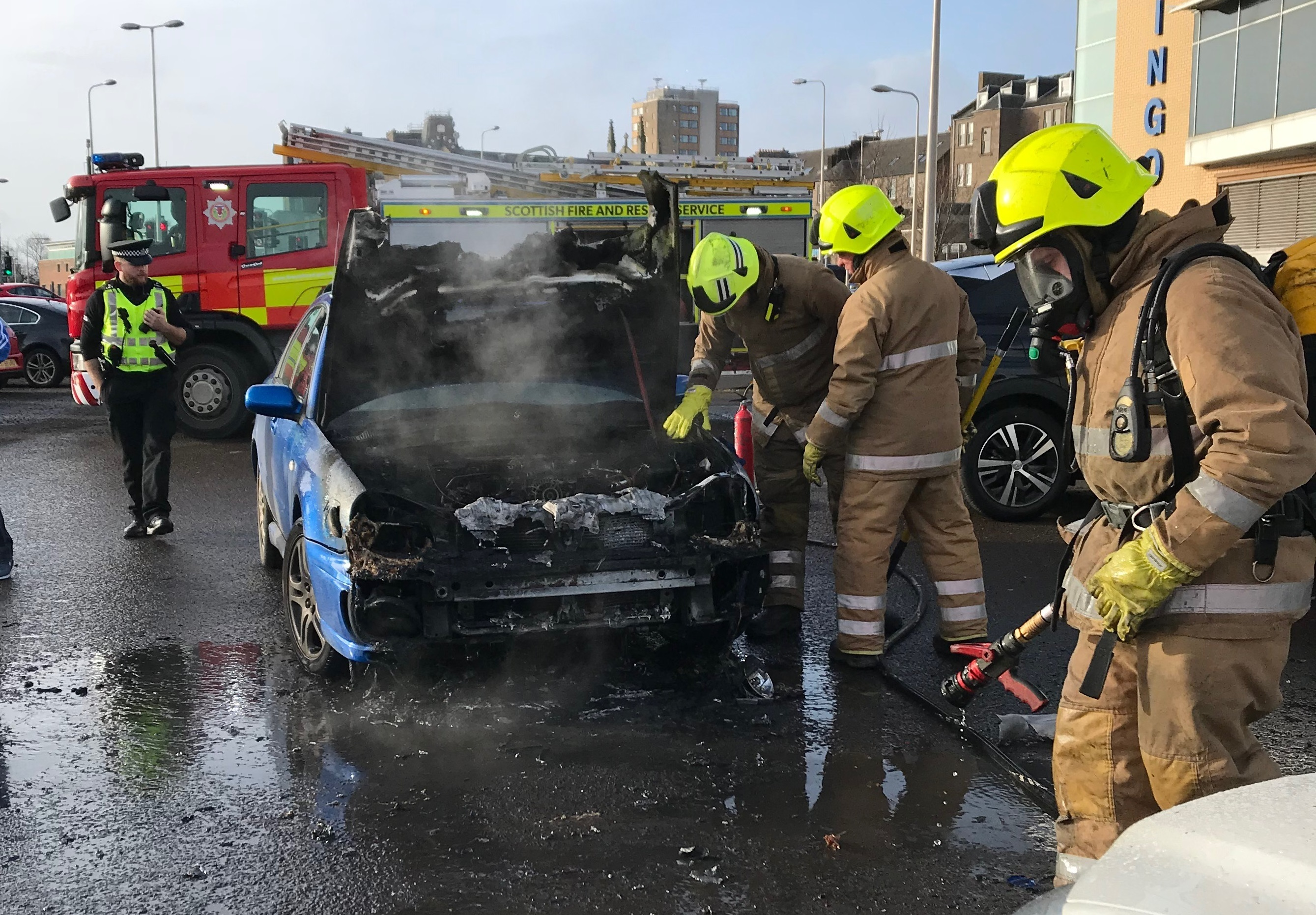 Firefighters dowse down the burnt-out remains of the Subaru Impreza.