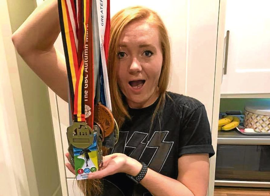Jenna with medals from her 17 marathons