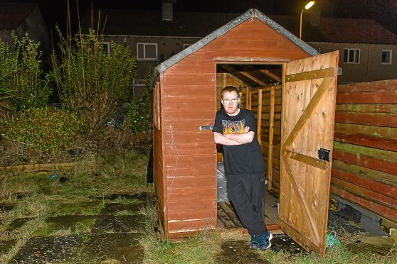 Jason Kerrigan, 30, at the shed from which his £500 Carrera bike was stolen on Monday night.