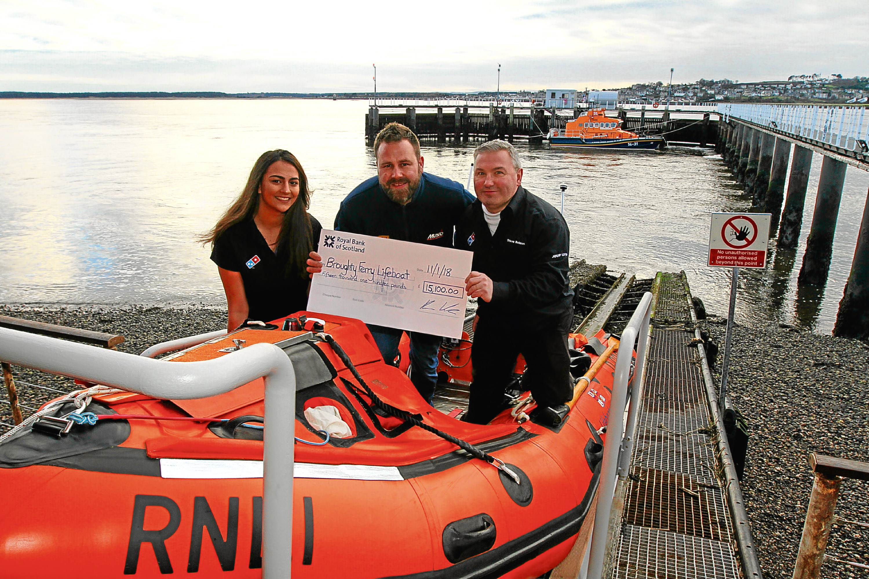 Steve Robson and Yasmin Thoms, from Domino's, presenting the cheque for £15,100 to Kenny Watson of the RNLI, at the lifeboat house in Broughty Ferry