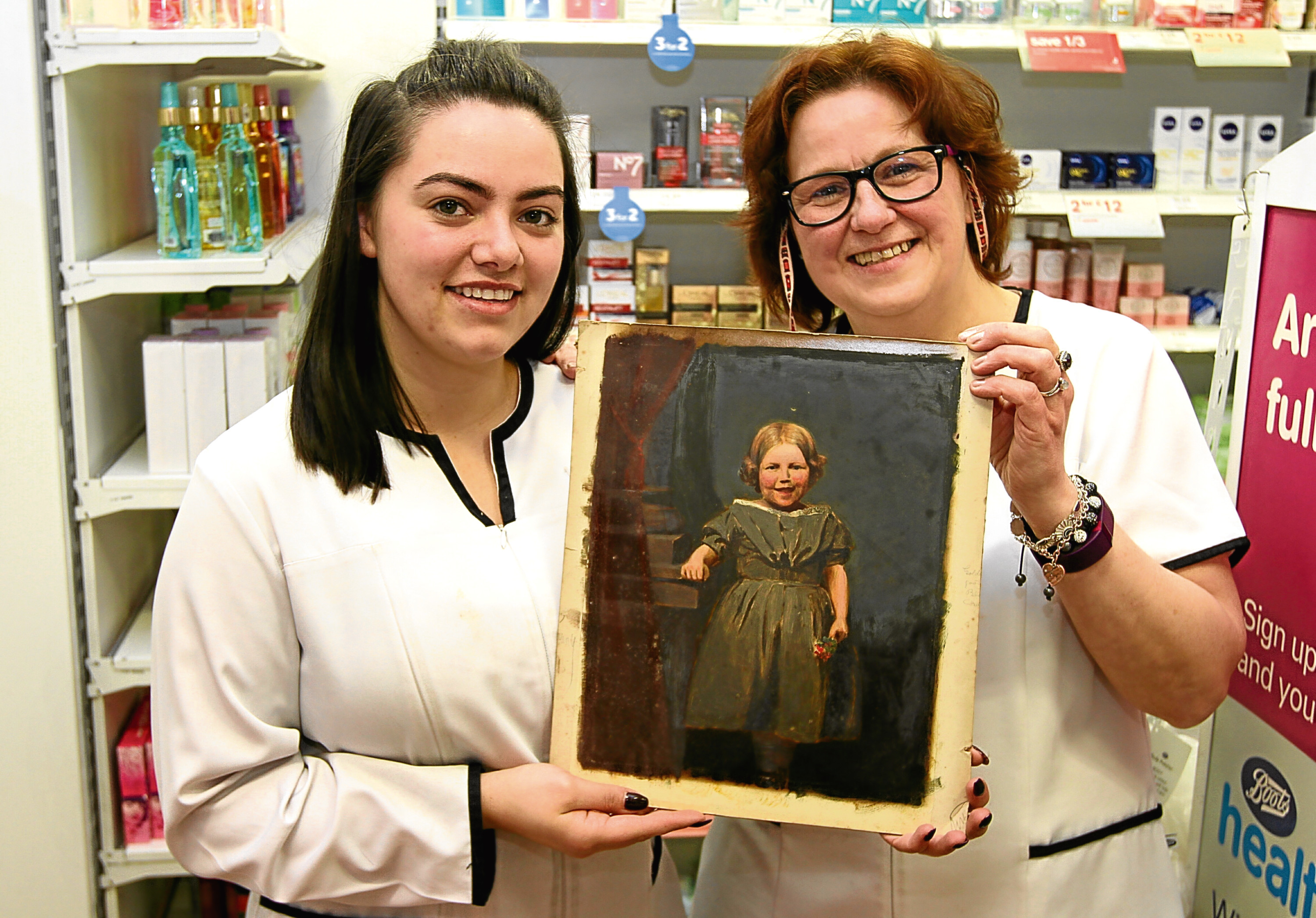 Dispensing assistant Georgette Low (right) and pharmacy technician Jessica Low with the mystery painting