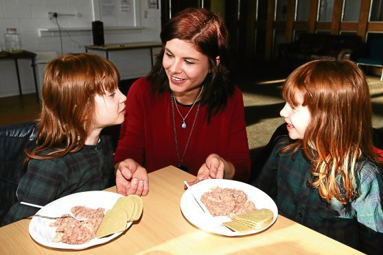Manager Daniélle Gaffney Du Plooy with identical twins Abigail and Caitlin Young, 5, with their stovies