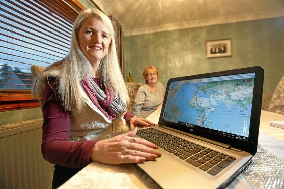 Donna Boylan maps out her epic journey at her parents' house in Balumbie, watched by mum Cath.