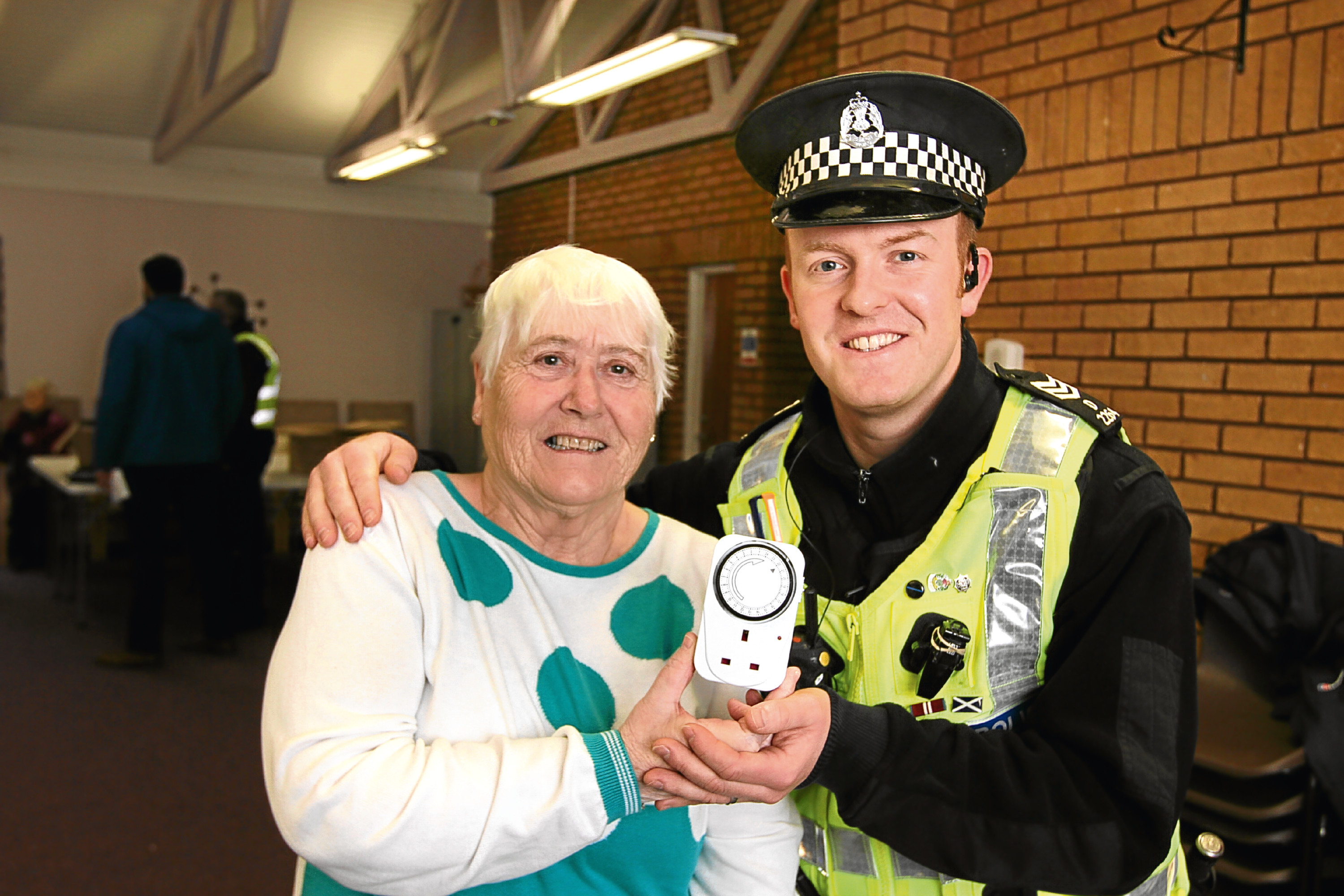 Margaret Mackay receives a light timer from Sergeant Jamie Webster at Forthill Sheltered Housing Complex.