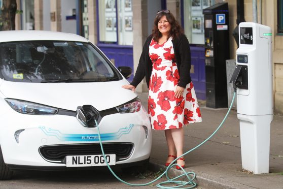 Councillor Lynne Short beside one of the electric vehicles which are proving popular in Dundee.