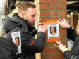 Eamonn Colgan puts up missing person posters in Hamburg asking for help to find his brother Liam