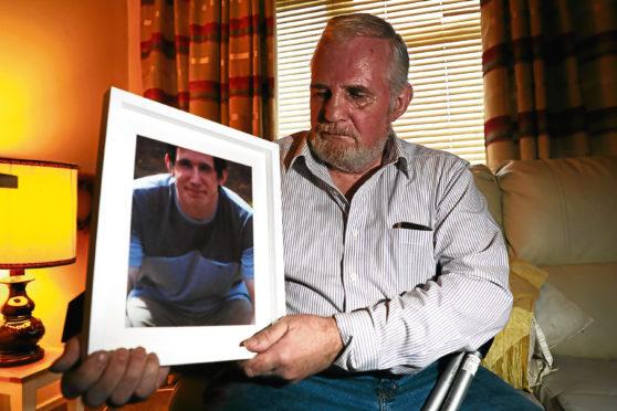 Ian Robertson with a picture of his son.