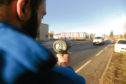 Reporter Adam Hill using the speed gun on at the 20mph zone on Harestane Road, outside Baldragon Academy.