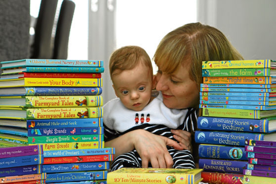 Mum Nicola at home with Leo alongside a pile of books set for the hospital