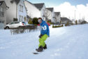 Snow boarder Kevin Trueland rides down Balmossie Road, Dundee in the deep snow last month