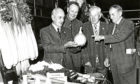 Mr A. Simpson holds a giant onion which is much admired by Mr J. Dawson, section winner, Mr A. Dodds & Mr A Tosh, at the Dundee Flower Show. 2 September 1977.