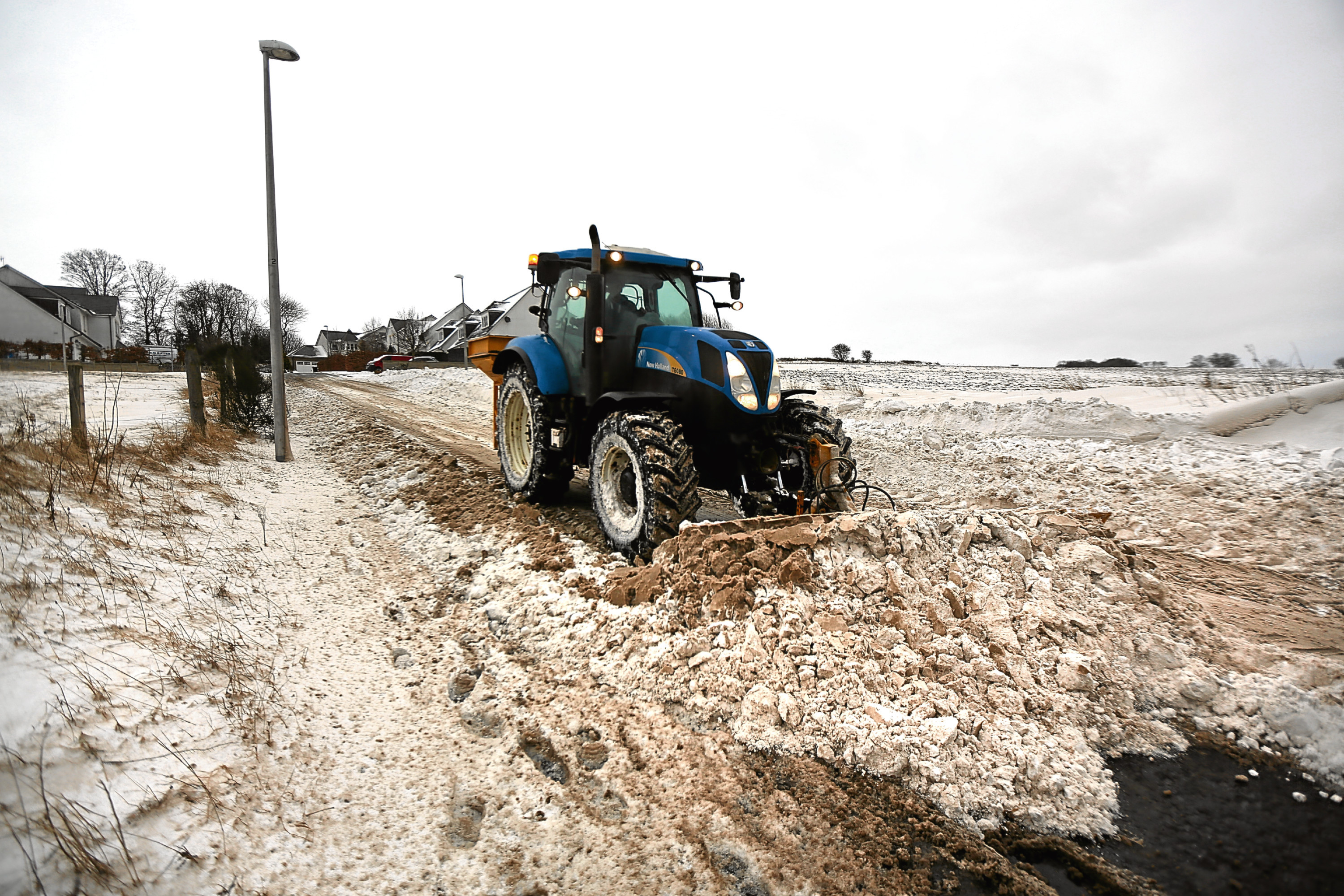 A tractor clearing deep snow drifts on Balmossie Brae