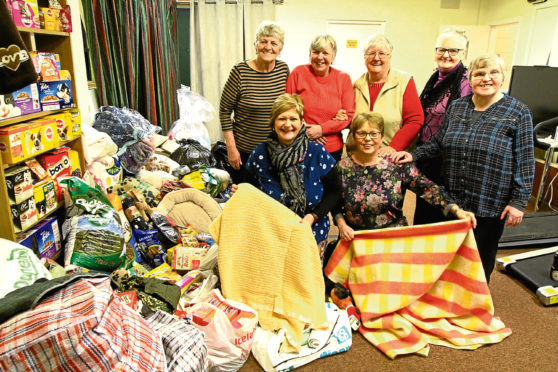 Patricia and Doreen (front, kneeling) with some of the Deaf Hub service users, beside the piles of blankets and food
