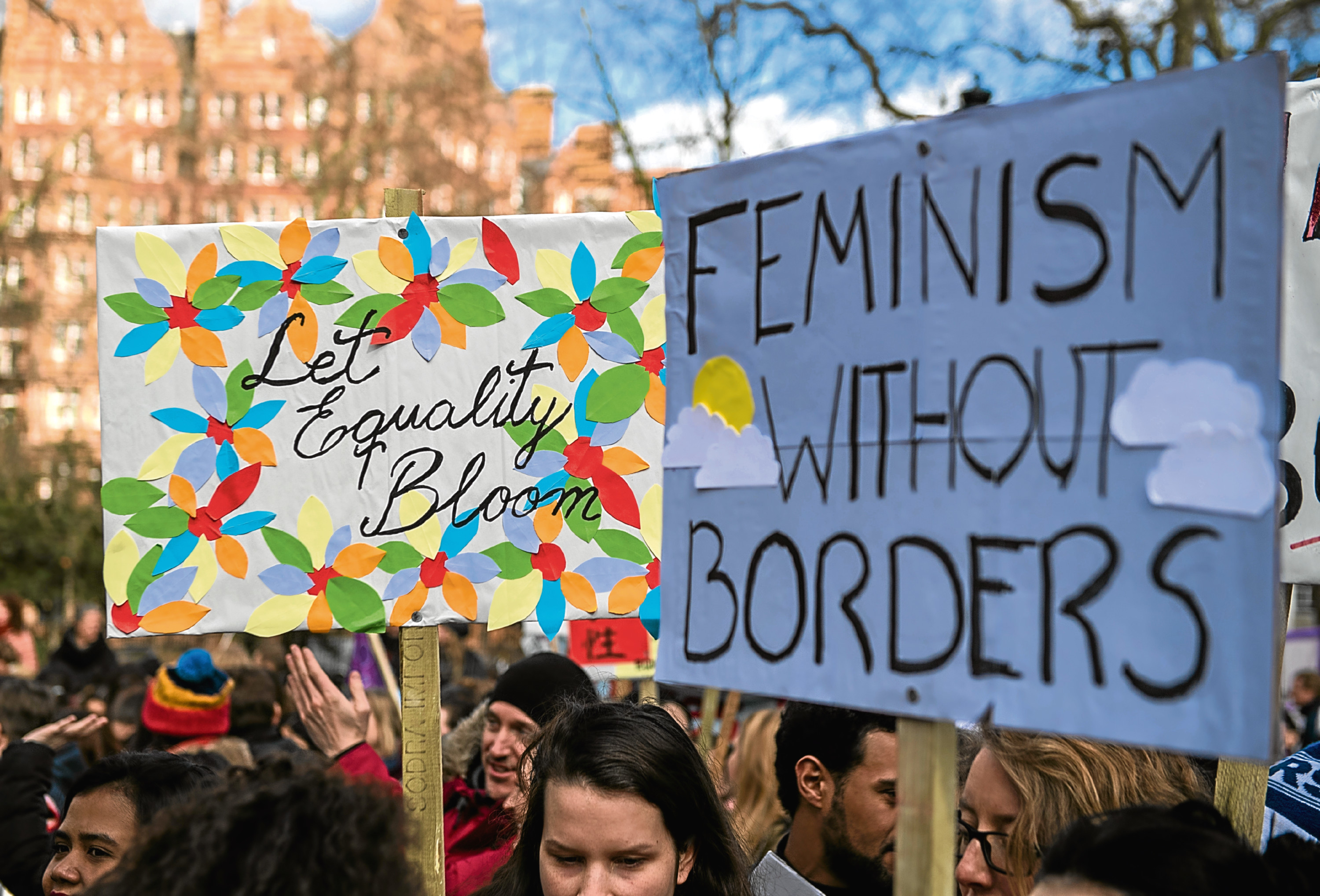 Women's rights demonstrators hold placards during a rally to mark International Women's Day