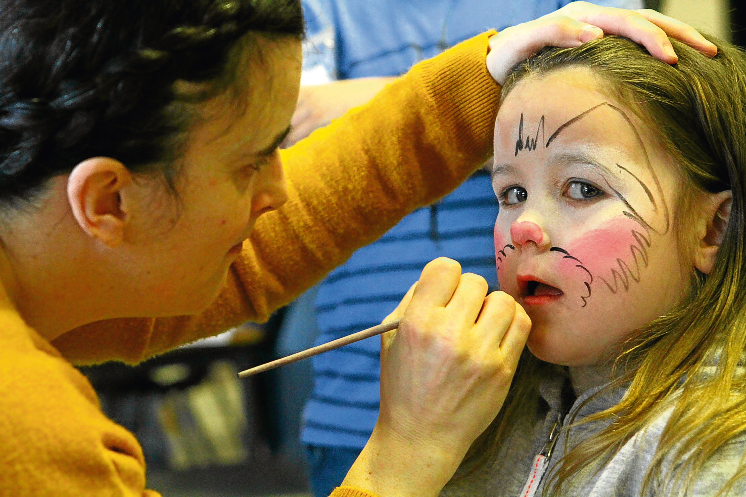 Katie Ramsay having her face painted by Laura Lawson