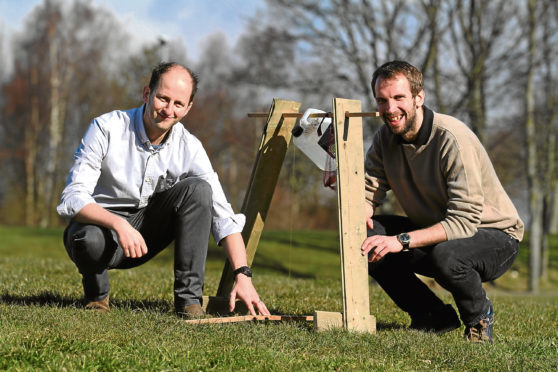 Signpost International's Jamie Morrison, left, and Michael Calder working on a Tippy Tap, is an easy solution for running water