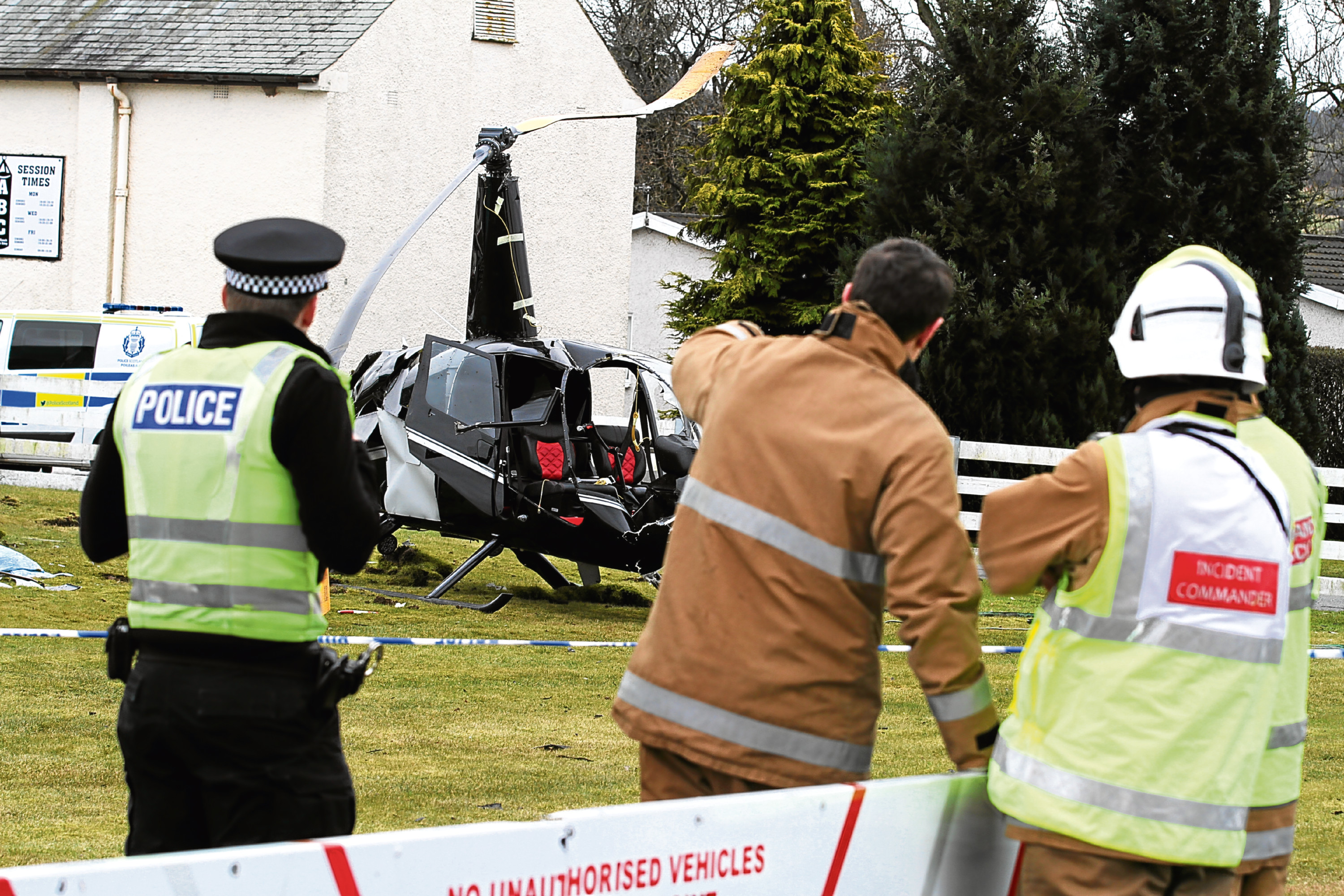 The crashed helicopter, with fire crews, police and other personnel dealing with the incident
