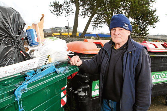 Charlie Melville next to the bins that were set on fire