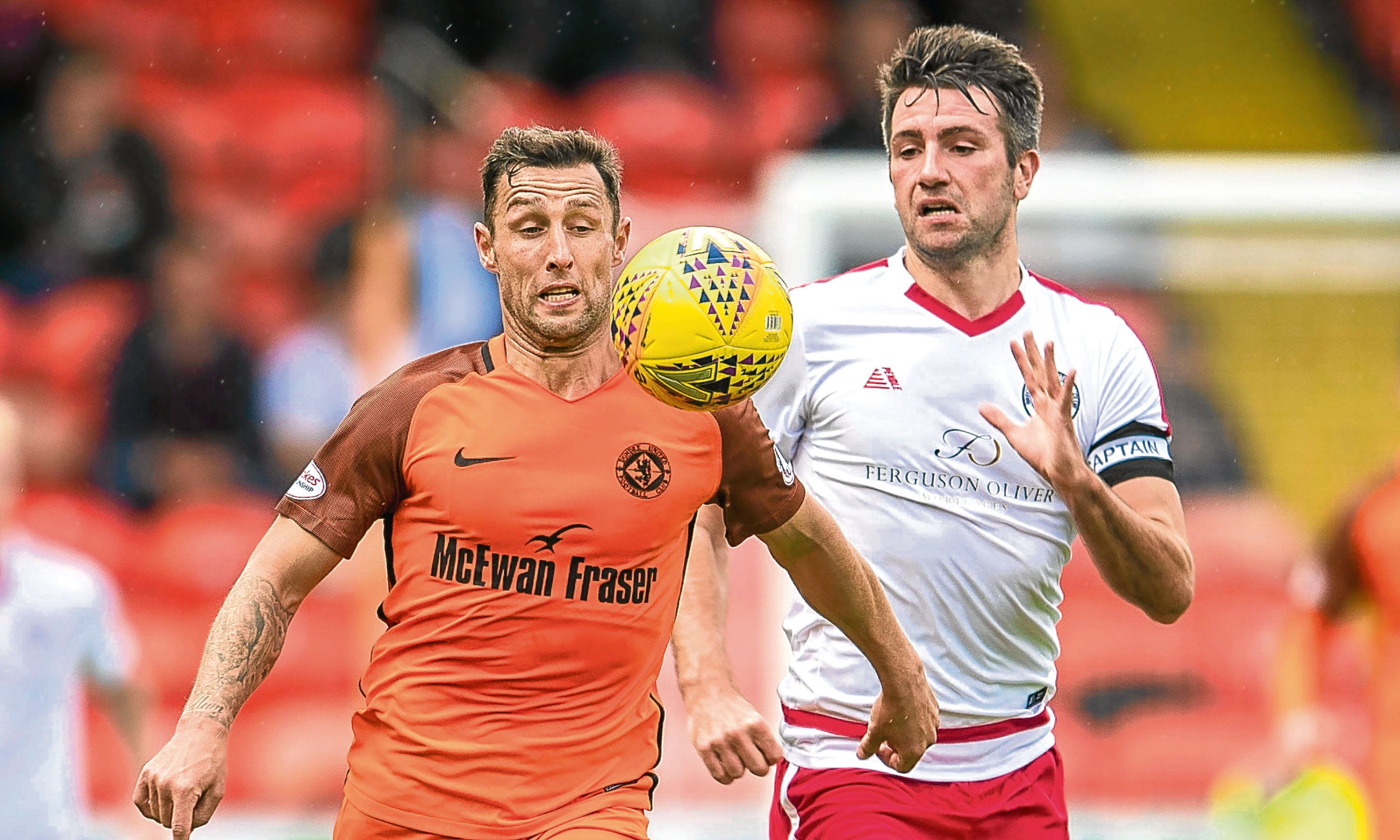 Dundee United's Scott MacDonald (left) takes on Brechin's Paul McLean
