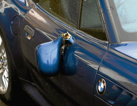 A wing mirror hanging off a BMW parked in Stobswell