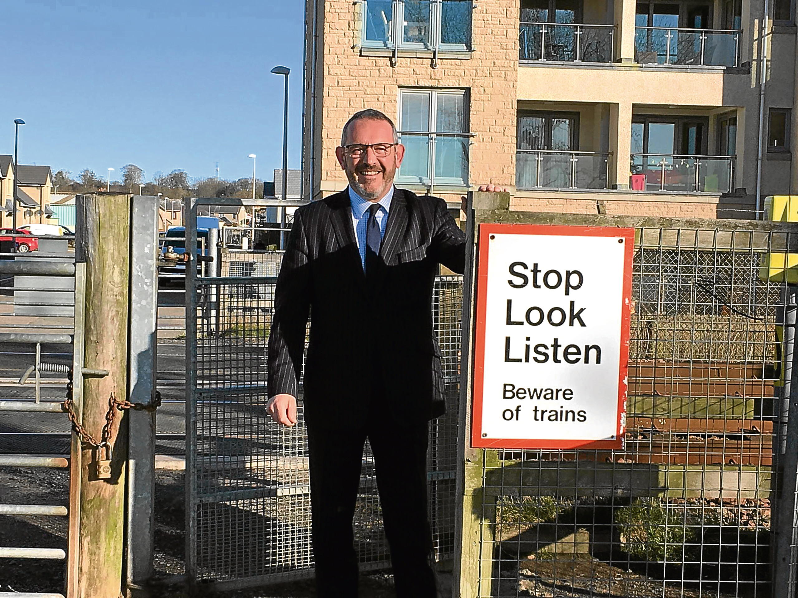 Mr Hosie is pictured at the repaired railway crossing gate.